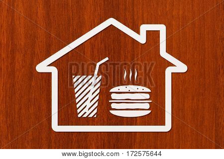 Paper house with burger and beverage inside on wooden background fastfood concept. Abstract food conceptual image