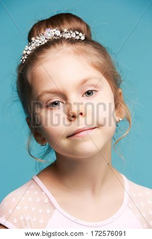 Cute little girl on a blue studio background close-up