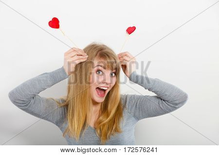 Love and fun concept. Lovely enjoyable smiling woman playing with two little red hearts on sticks. Playful joyful attractive blonde girl portrait.
