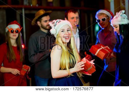 Young peoples christmas party. Gathering a lot of gifts in the nightclub