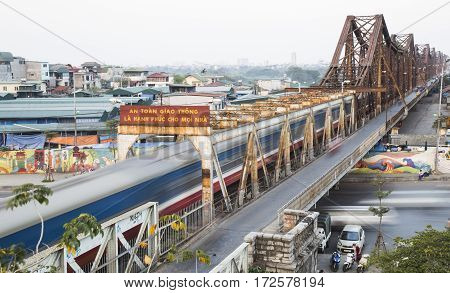 Hanoi, Vietnam - Feb 18, 2017: Old diesel engine train running on Long Bien bridge over Hong (Red) river. The bridge was designed by French architect Gustave Eiffel in time French ruled Vietnam.