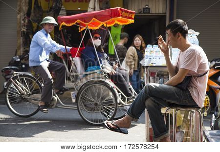 Hanoi, Vietnam - Feb 19, 2017: Vietnamese man smoking while selling drinking bottles to travelers on the side walk of a street in Hanoi old 36 quarter street, and a cyclo passing behind.