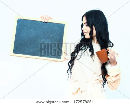 Smiling Girl In Beige Bathrobe Holding Board And Cup