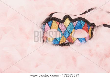 Colorful venetian carnival mask lying on a pink feathers boa