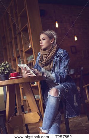 Beautiful young blonde sitting in a cafe pensive having a morning coffee holding a tablet computer and posting to the Internet