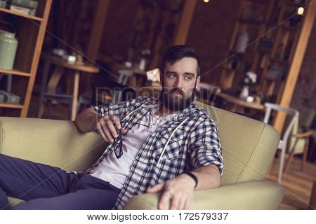 Handsome hipster sitting in an armchair in a cafe holding his glasses and looking at the distance