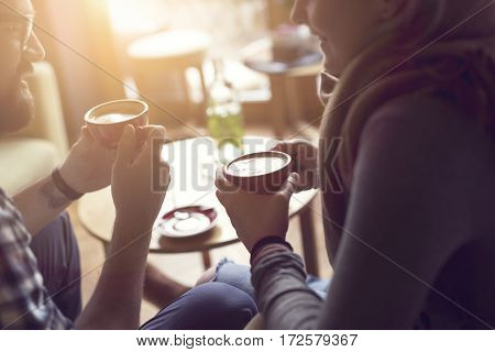 Young couple in love sitting in a cafe drinking coffee having a conversation and enjoying the time spent with each other. Selective focus