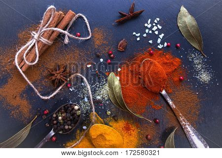 Different culinary spices on a black background. Bay leaf, turmeric, paprika, star anise, cinnamon sticks, colored pepper. Top view