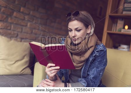 Beautiful modern girl sitting in an armchair and reading a book