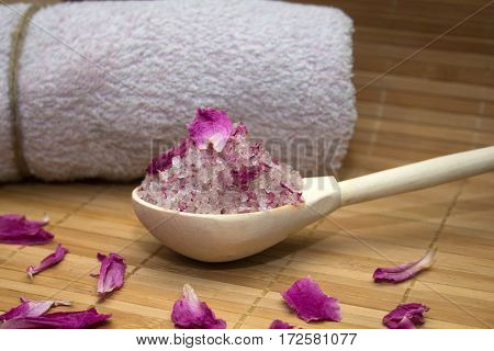 homemade body scrub from sea salt and rose petals and peony pink towel on a straw Mat. Spa concept