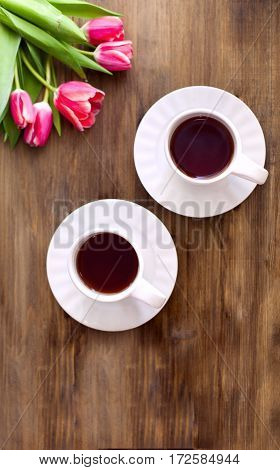 Pink tulips on wooden background two cups of tea and coffee on saucers with hearts marmalade.