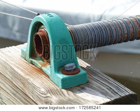 An old cable wind for a slips sling with boat in dry dock.
