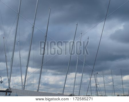 Sail boat mast rise from sail boats in dry dock against a stormy sky.