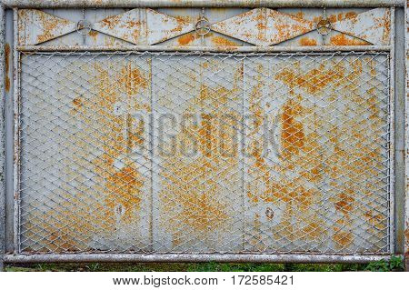 old rusty fence of metal sheets and metal mesh with the remnants of gray paint