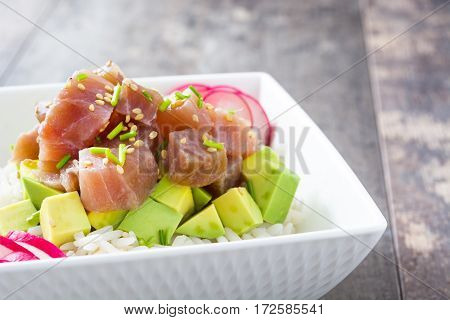 Hawaiian tuna poke bowl with avocado, radishes and sesame seeds on wooden background