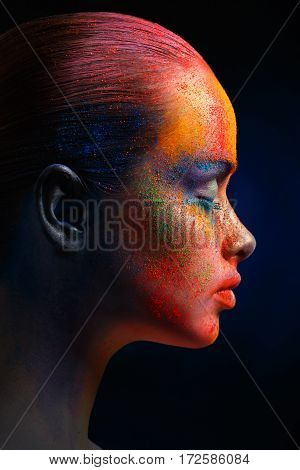 Creative art make up. Closeup cropped studio portrait of young fashion model with bright colorful mix of paint on her face. Color fantasy, artistic makeup. Side view or profile, vertical