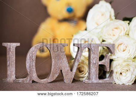 A word LOVE made of wood, white roses flowers and a yellow teddy bear in blue bow tie background.