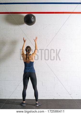 Photo of a woman exercising by throwing a medicine ball up against a wall in a gym.