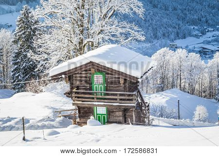 Beautiful view of traditional wooden mountain chalet embedded in scenic white winter wonderland mountain scenery in the Alps on a cold sunny day