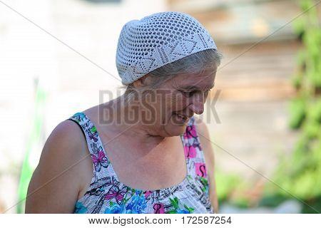 an elderly woman in the garden outdoors in dress