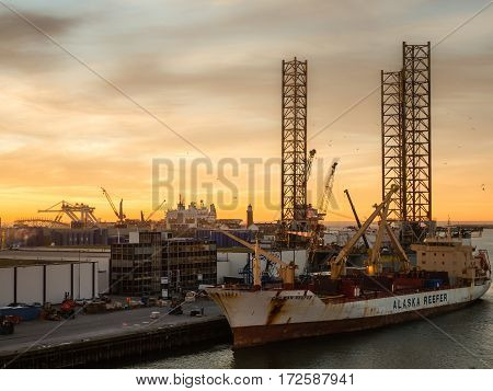 IJMUIDEN. NETHERLANDS - 20 JAN. 2017: Sun sets over the port of IJmuiden, Netherlands. In the foreground lies Chilean Reefer, a refrigerated cargo ship waiting to depart to Lithuania