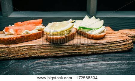 Toasts of bran bread with cottage cheese. Colorful fresh fruit toppings