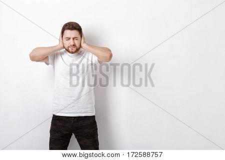 portrait of a young Brunet man in white shirt covers his ears with his hands against a grey background. I don't want to hear anything