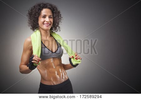 Happy smiling fit woman posing with a green towel on grey background