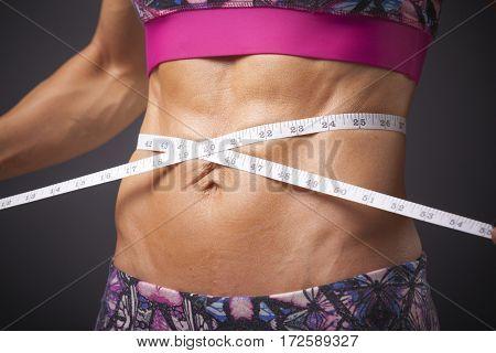 Athletic slim woman measuring her waist by measure tape