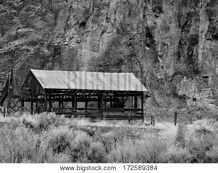 An empty old and worn hay storage building in Eastern Oregon on an abandoned ranch beneath a cliff on a winter day.