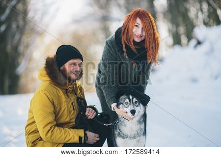 couple playing with the dog in the park in winter