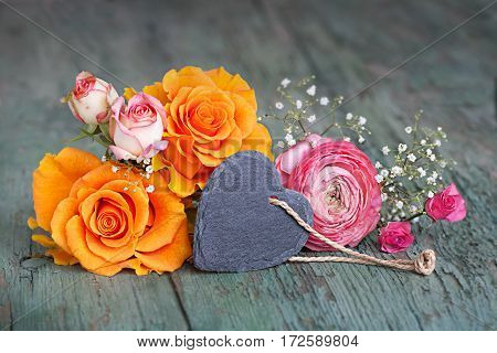 Decoration with colorful roses and a heart from slate on an old shabby wooden table for mothers day
