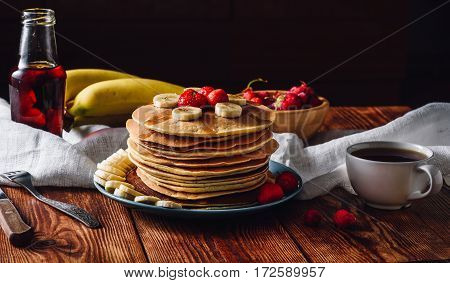 Homemade Pancakes with Fruits Maple Syrup and Cup of Tea.