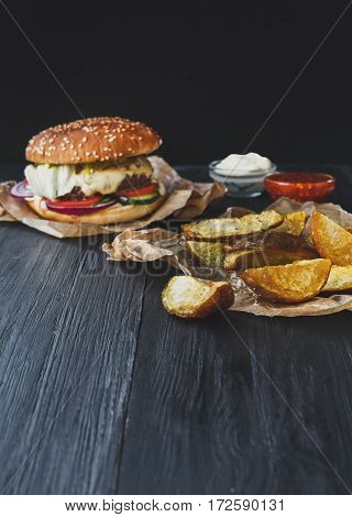 Fast food restaurant dish. Meat cheese burger in craft paper, potato chips and wedges. Take away set on dark black wood background. Hamburger and tomato sauce. Vertical, filtered