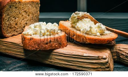 Wholemeal bread loaf and toasts with farmer cheese on rustic wood board