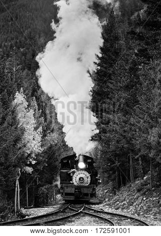 Vintage steam train climbing a hill in Colorado