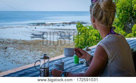 Women Morning Coffee near Seaweed Plantations algal, fisherman boats in background - Nusa Penida, Bali, Indonesia.