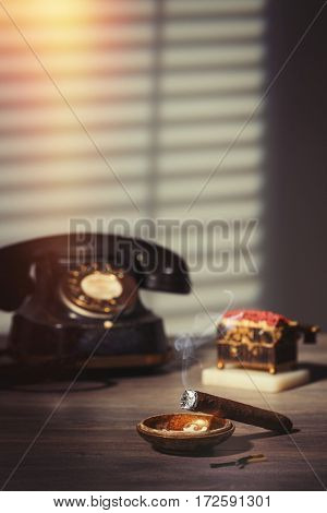 Lit cigar smoking in an ashtray.  Antique vesta box and vintage telephone in the background