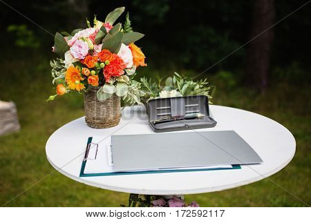 Beautiful unusual wedding decor. Rustic Style. Pen in a case the layout on the table. Flowers in a basket.