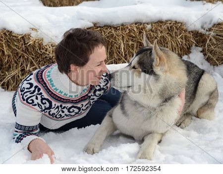 woman play with dog on snow