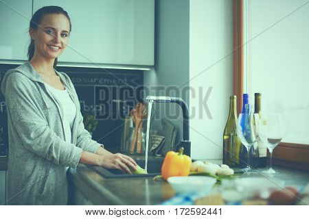 Beautiful young woman washing vegetables for salad while standing in the kitchen