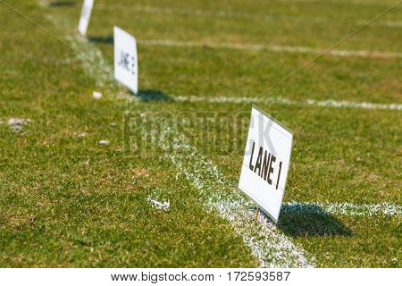 Lane signs on grass field for elementary school track and field tournament
