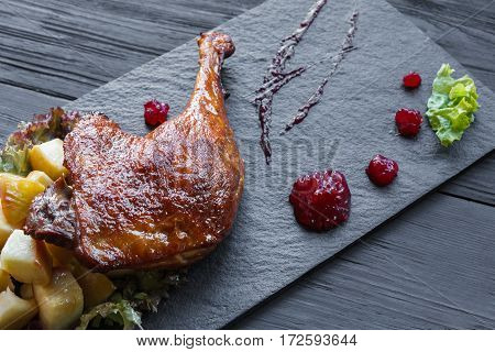Roasted duck leg closeup, served on slate plate with apples, lettuce and cherry sauce. Restaurant food on black wood table