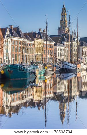 GRONINGEN, NETHERLANDS - FEBRUARY 15, 2017: Old ships and church tower along a canal in Groningen, Neherlands