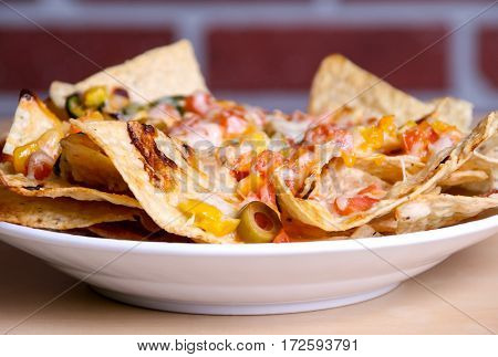 loaded cheese nacho plate on table brick wall background