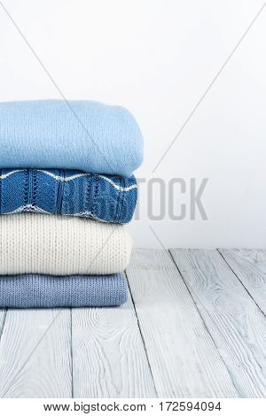 Knitted wool sweaters. Pile of knitted winter autumn clothes on white wooden background sweaters knitwear space for text.