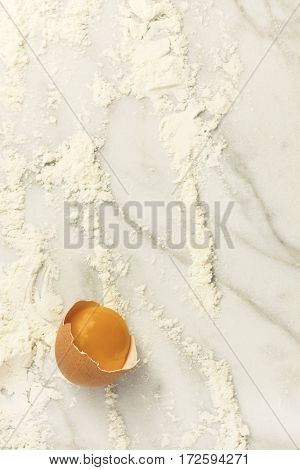 A photo of an egg with traces of flour, shot from above on a white marble texture with a place for text