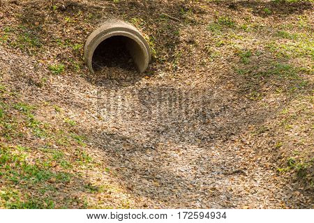 dry drainage pipe with fallen leaves showing danger sign of drought and shortage of water
