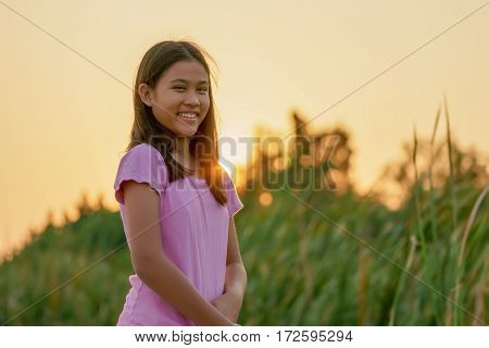 Portrait of a cute little girl smiles looking at camera in sunset