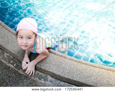 Asian girl is playing in the pool laying down